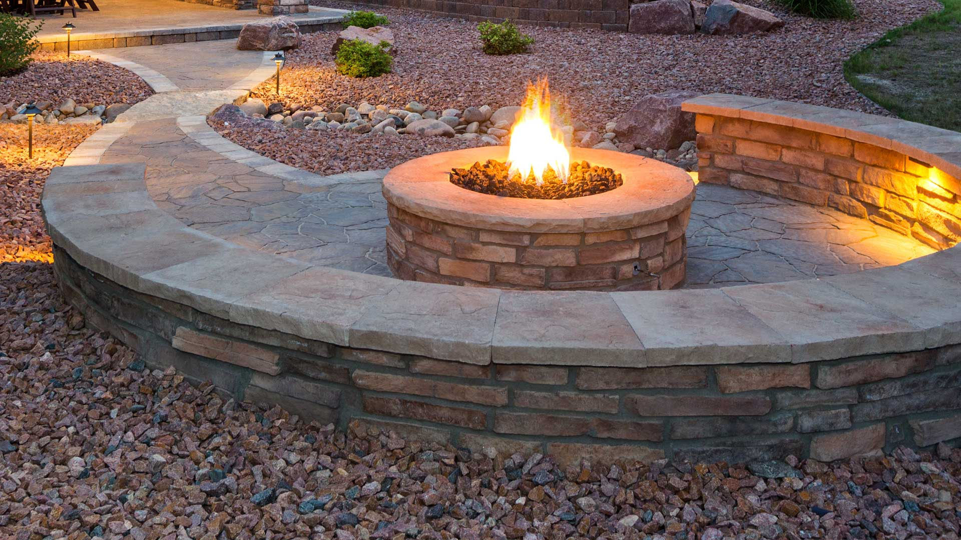 Fire pit with a retaining seating wall surrounding it at a home in Kingston, NY.